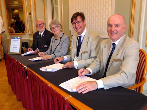 Signing the Master Contract: left to right: Brian Allen, Chairman Guernsey IGA; Dame Mary Perkins, Chair, 2021 Organising Committee; Jorgen Pettersson, Chairman IIGA; James Johnston Vice-Chairman IIGA. Photo by Bob Kerr